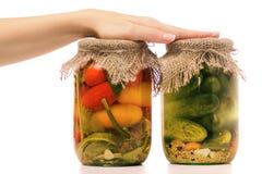 Консервация банка огурцов и банка руки женщины томатов стоковые фото
