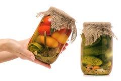 Консервация банка огурцов и банка руки женщины томатов стоковые изображения