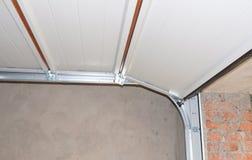 Консервооткрыватель двери гаража устанавливать и ремонта и поднимаясь система стоковые изображения