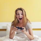 Консоль девушки предназначенная для подростков играя сидя вверх в кровати Стоковая Фотография RF