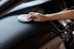 Консоль черноты кожи чистки руки женщины в автомобиле Стоковые Фотографии RF