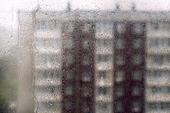 Конспект капелек воды на окне с предпосылкой зданий города в идти дождь день запачкал здания Стоковая Фотография