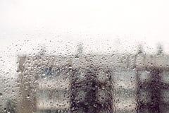 Конспект капелек воды на окне с предпосылкой зданий города в идти дождь день запачкал здания Стоковые Фото
