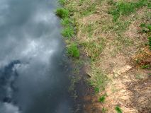 Конспект, облака и голубое небо отраженные на озере отделывают поверхность Стоковая Фотография RF