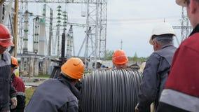 Конструктивные слесарь-монтажники разматывают веревочку стального провода от катушкы на земле видеоматериал