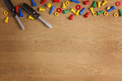 Конструкция детей забавляется инструменты: красочные отвертки, винты и гайки на деревянной предпосылке Взгляд сверху Плоское поло Стоковые Изображения
