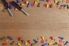 Конструкция детей забавляется инструменты: красочные отвертки, винты и гайки на деревянной предпосылке Взгляд сверху Плоское поло Стоковое Изображение