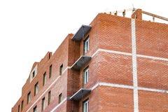 Конструкция жилого дома высотного здания красного кирпича на белой предпосылке Стоковые Фото