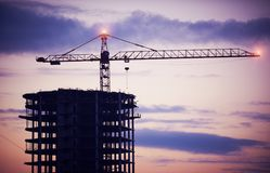 Конструкция здания кранами на ноче Стоковое Фото