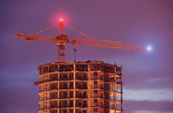 Конструкция здания кранами на ноче Стоковые Фото