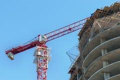 конструкция кирпичей кладя outdoors место Краны и многоэтажное здание конструкции под конструкцией против голубого неба Стоковая Фотография RF