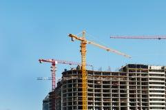 конструкция кирпичей кладя outdoors место Краны и многоэтажное здание конструкции под конструкцией против голубого неба Стоковые Фото