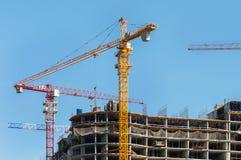 конструкция кирпичей кладя outdoors место Краны и многоэтажное здание конструкции под конструкцией против голубого неба Стоковое фото RF