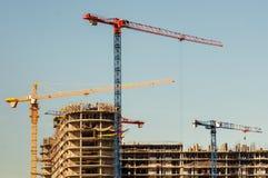конструкция кирпичей кладя outdoors место Краны и многоэтажное здание конструкции под конструкцией против голубого неба Стоковое Фото