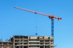 конструкция кирпичей кладя outdoors место Краны и многоэтажное здание конструкции под конструкцией против голубого неба Стоковое Изображение