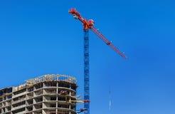 конструкция кирпичей кладя outdoors место Кран и многоэтажное здание конструкции под конструкцией против голубого неба Стоковое Фото