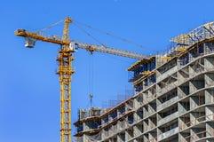 конструкция кирпичей кладя outdoors место Кран и многоэтажное здание конструкции под конструкцией против голубого неба Стоковая Фотография RF