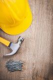 Конструкция молотка с раздвоенным хвостом пригвождает шлем здания на деревянной доске Стоковые Фотографии RF