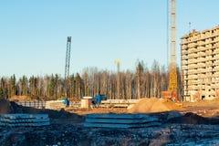 Конструкция нового здания мульти-этажа окруженного лесами Краны конструкции против голубого неба стоковые фото