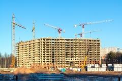 Конструкция нового здания мульти-этажа окруженного лесами Краны конструкции против голубого неба стоковое изображение
