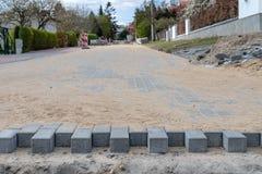 Конструкция новой дороги от бетонных плит Новые вклады в небольшом городе в Центральной Европе стоковое изображение rf