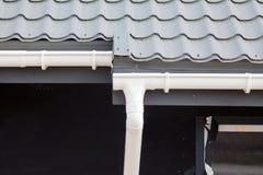 Конструкция дома панели ГЛОТОЧКА Новая серая крыша плитки металла с белой сточной канавой дождя Стоковые Изображения RF