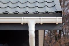 Конструкция дома панели ГЛОТОЧКА Новая серая крыша плитки металла с белой сточной канавой дождя Стоковая Фотография