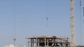 Конструкция рамки здания сделанной из бетона На рабочий-строителях двигайте, крюк крана башни отбрасывает видеоматериал