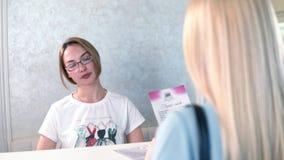 Консультант бутика платья говорит информацию к клиенту на столе видеоматериал