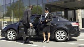 Консультант выставочного зала автомобиля показывая к автомобилю покупателя роскошному, говоря о своем профи видеоматериал