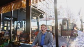 Консультант говоря с клиентом на кафе используя телефоны таблетки и шлемофона с микрофоном n акции видеоматериалы