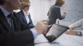 Консультант дамы делая представление для коллег на отделе рекламы и стимулирования сбыта видеоматериал