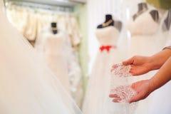 Консультант показывает шнурок на предпосылке платьев свадьбы стоковая фотография