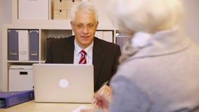 Консультант говоря к пожилому клиенту в офисе акции видеоматериалы