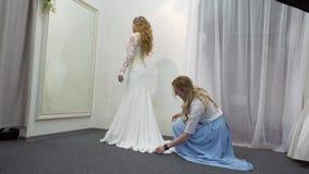 Консультант помогает будущей невесте выбрать платье свадьбы сток-видео