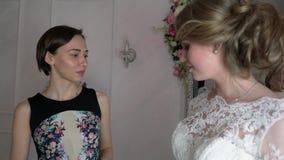 Консультант помогает будущей невесте выбрать платье свадьбы видеоматериал