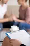 Консультировать пар Женский psychotherapist с доской сзажимом для бумаги и ha стоковые фото