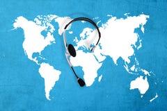 Контактируйте глобальную концепцию, шлемофон взгляд сверху и карту Стоковая Фотография