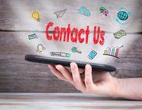 контактируйте почту позвоните по телефону нам планшет в руке деревянное предпосылки старое стоковые фото