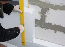 Контактор устанавливая твердую изоляцию доски стиропора на стену дома для энергосберегающего стоковая фотография rf