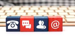 Контакт значит значки на деревянной кости с клавиатурой в предпосылке Стоковое Изображение
