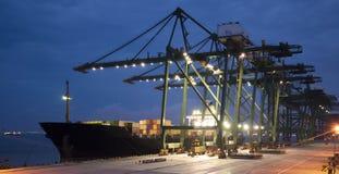 Контейнеры загрузки грузового корабля к ноча стоковое изображение