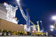 Контейнеры загрузки грузового корабля к ноча Стоковые Изображения RF