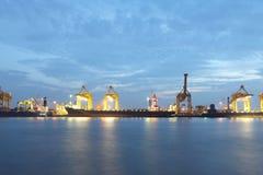 Контейнеры нагружая на море порт торговой операции на сумерк Стоковые Фото