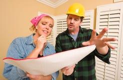 контрактор обсуждая трудный шлем планирует женщину Стоковое Изображение