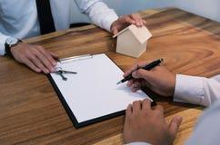 Контракт бизнесмена подписывая делая дело с временем недвижимости Стоковое Изображение RF