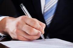 Контракт бизнесмена подписывая на столе Стоковые Изображения