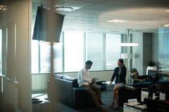 Контракт бизнесмена подписывая пока сидящ на софе в офисе Стоковая Фотография RF