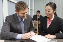 Контракт бизнесмена подписывая с азиатской коммерсанткой Стоковое Фото