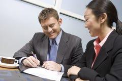Контракт бизнесмена подписывая с коммерсанткой Стоковое Изображение